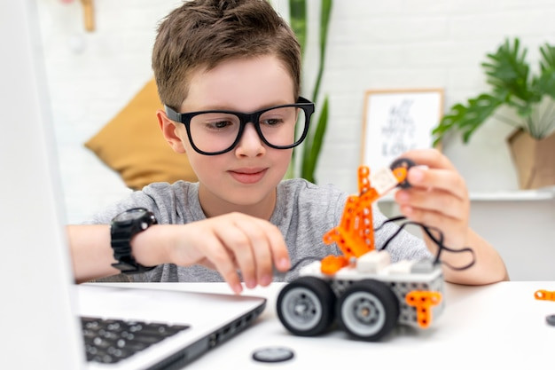 Child learns coding on a laptop boy looks at the robot car and fixes the control sensors