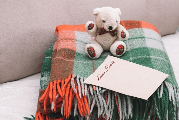 Child letter to santa claus on old paper with place for greeting with a teddy bear on a red-green plaid blanket