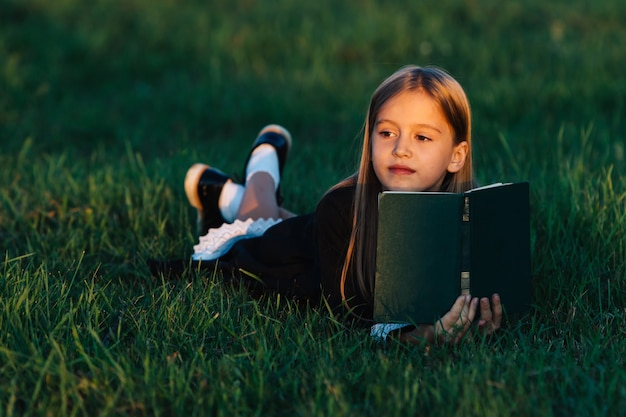 The child lies on the grass and holds a book in the sunset light.