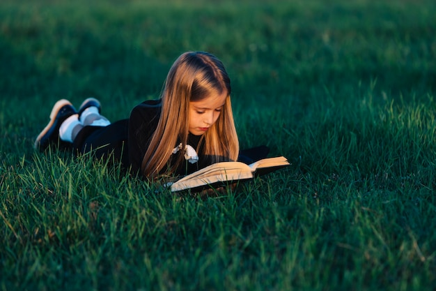 A child lies on the grass and reads a book in the sunset light.