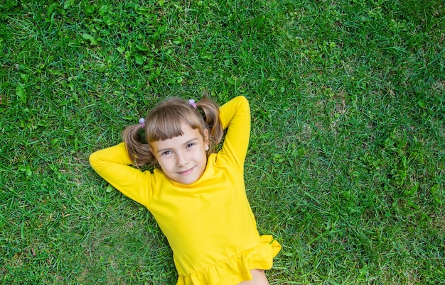 The child lies on the grass.