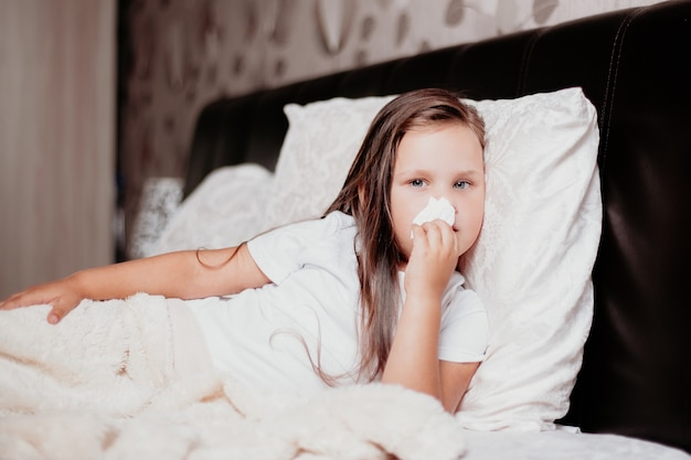 A child lies on a kravat and wipes snot with napkins, the second wave of the covid-19 virus.
