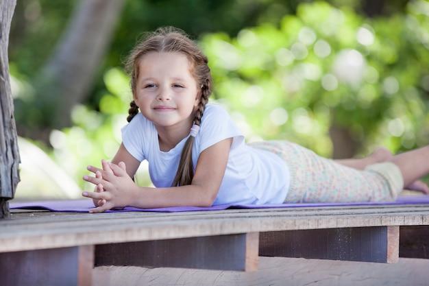 Ребенок лежит на деревянной платформе на открытом воздухе и мечтает.
