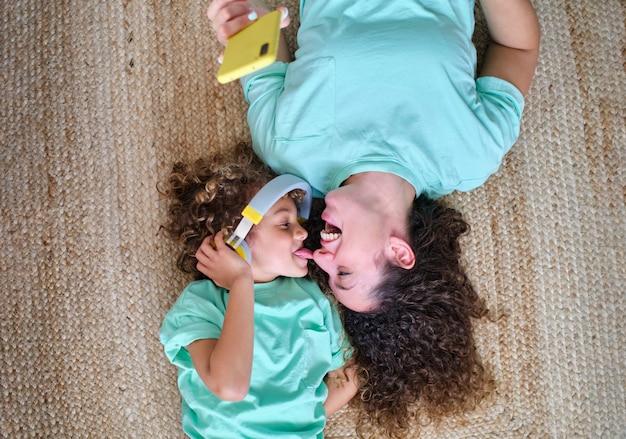 ヘッドホンで音楽を聴いている子供が母親の鼻に舌で触れ、敷物の上に横たわっている