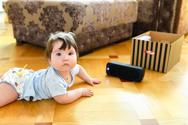 The child listens to a portable speaker system. listening to music from an early age