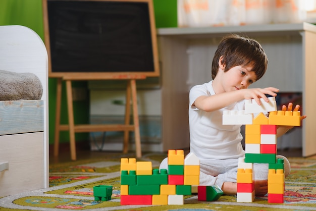 Child little boy playing with wooden cubes toys in nursery at home or daycare center