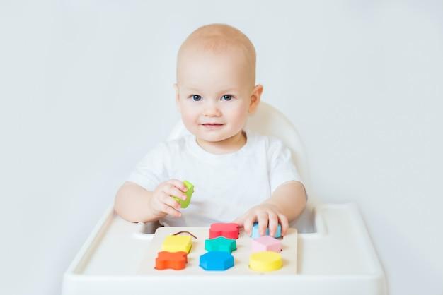 Ребенок маленький мальчик играет в деревянные игрушки дома или в детском саду