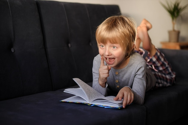 Child little boy reading a book while lying on the sofa