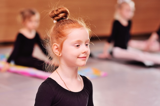 Child - little cute red-haired girl ballerina performs stretching exercises in ballet school