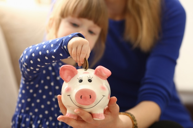 Child little girl arm putting coins into piggybank