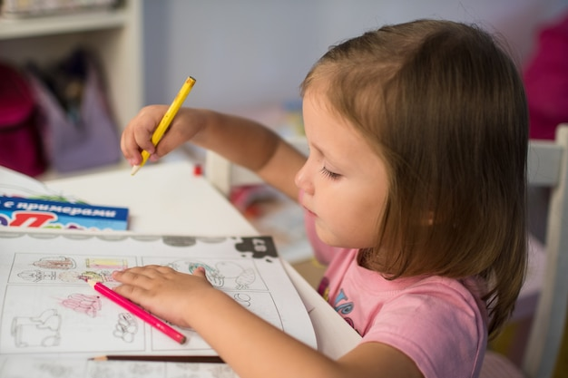 Маленькая девочка ребенка рисует карандаши дома