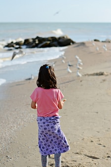 A child (little girl) feeds the birds on the seashore