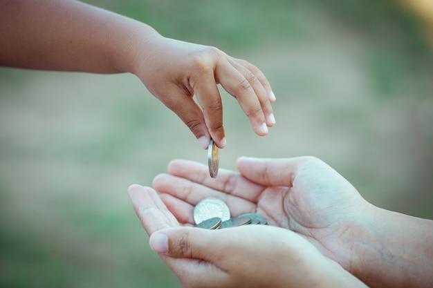 Маленькая девочка, дающая монету матери, как концепция экономии денег в старинном цветовом тоне