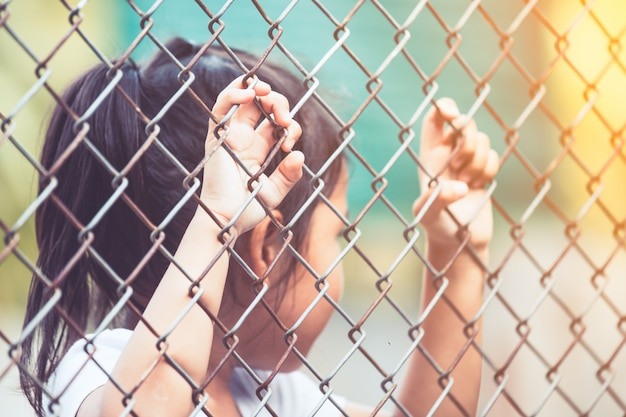 Child little girl hand holding steel mesh in vintage color tone