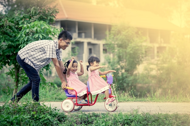 Child little girl having fun to ride tricycle with family
