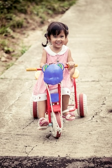 Child little girl having fun to ride tricycle with sister