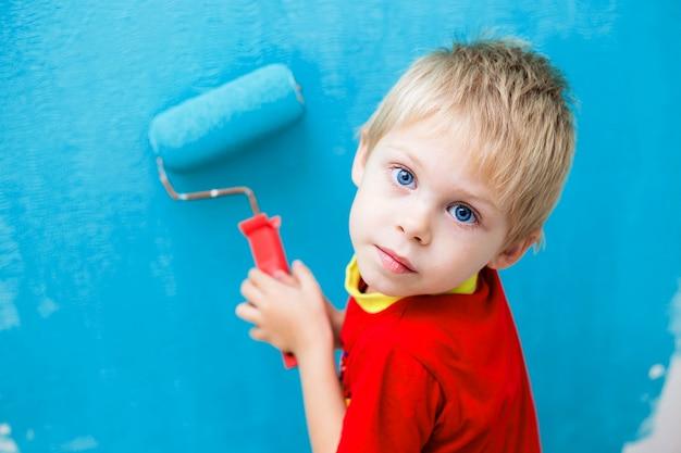 Ребенок, маленькая девочка красит стену роликами в синий
