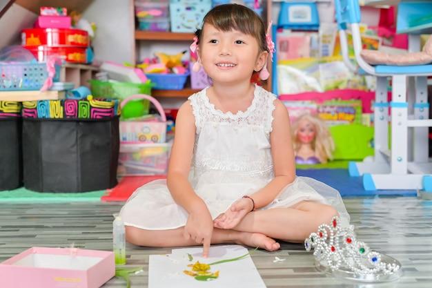 子供小さな女の子が自宅のリビングルームでおもちゃのアートを再生します。