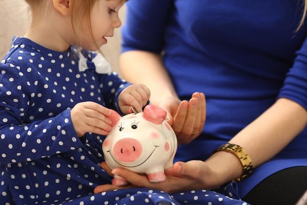 貯金箱にお金を入れている子供の小さな女の子