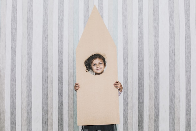 Детские маленькие девочки играют в космонавта с картонной ракетой