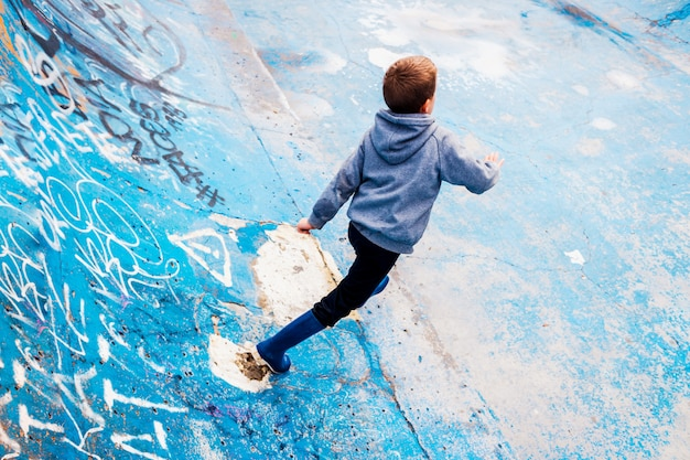 Child loitering inside an abandoned skating area, painted blue, and imagining able to skate.