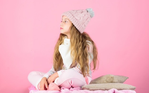 Child long hair warm woolen hat enjoy warm. kid girl wear knitted warm hat relaxing pink background. winter fashion warm clothes concept. warm accessories that will keep you cozy this winter.