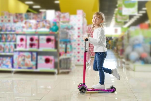 Ребенок смотрит на камеру и смеется во время езды на скутере