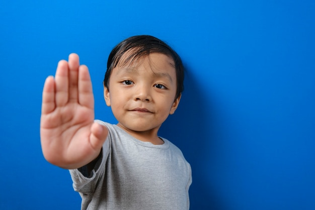 カメラを見ている子供。彼の手で信号を停止します。青い背景の上