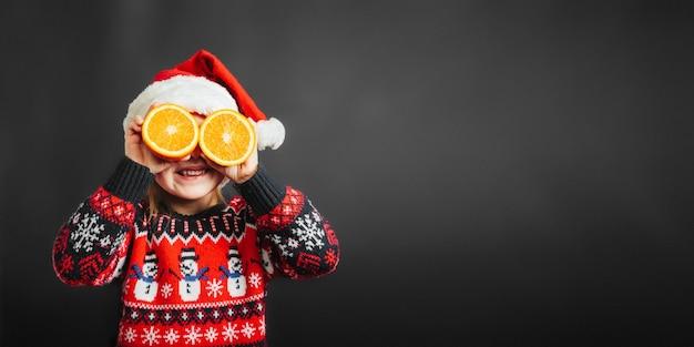 黒の背景にオレンジを通してクリスマスプレゼントを見ている子供