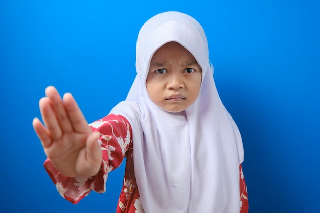 Child looking at camera. stop signal with her hand. over blue background