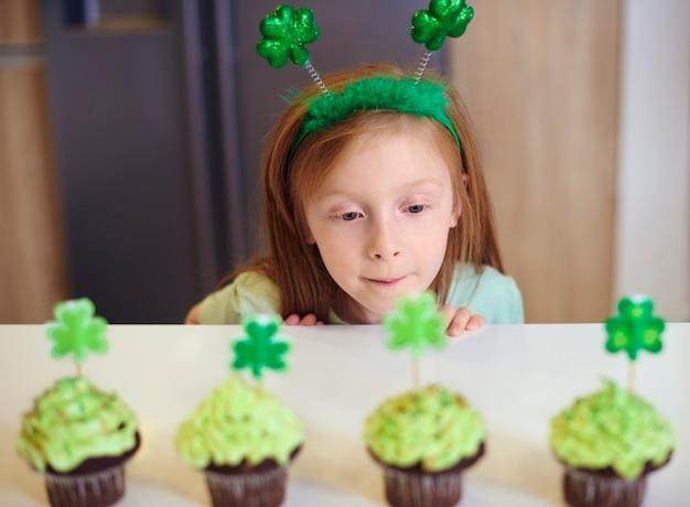Bambino che esamina deliziosi cupcakes