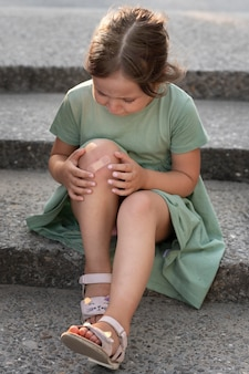Child looking at her knee injury
