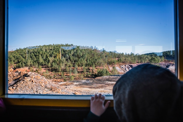 Child looking at nature from train