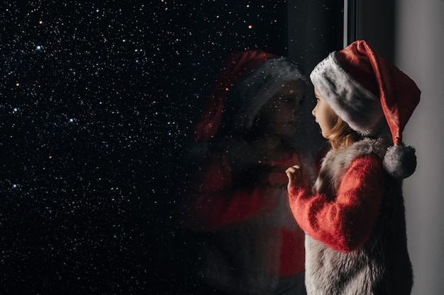 The child looks out the window on christmas of jesus christ.