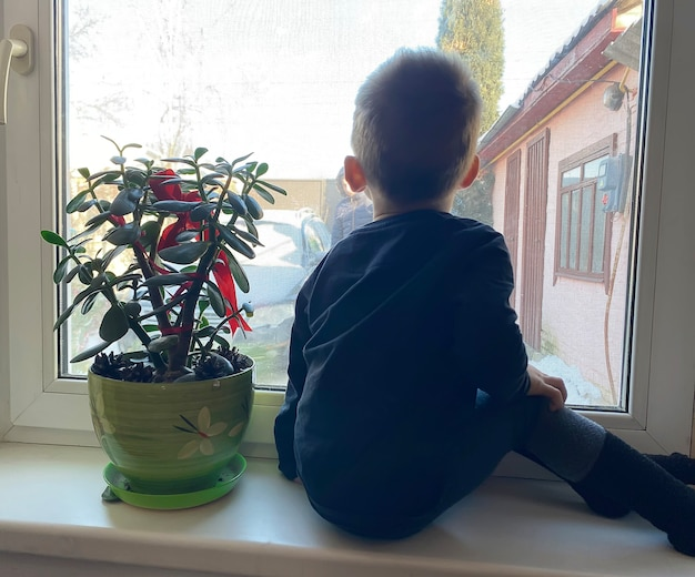 The child looks out the window and waits for parents from work. selective focus.