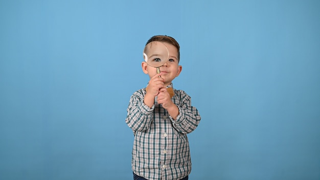 子供は虫眼鏡を通して見ます。高品質の写真
