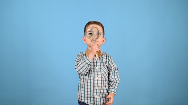 Child looks through a magnifying glass. high quality photo