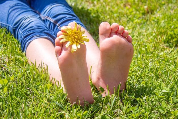 Ребенок лежал на зеленой траве. ребенок весело на открытом воздухе в весеннем парке. выборочный фокус. люди