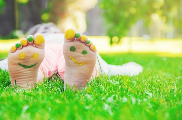 緑の芝生に横になっている子。春の公園で屋外楽しんでいる子供。