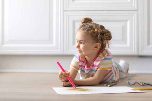 Ребенок, лежащий на деревянном полу, рисунок цветными карандашами смотрит на копировальное пространство хобби, игра, образование