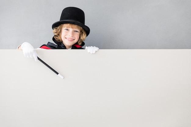 빈 포스터 뒤에 숨어있는 어린이 마술사.