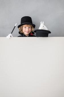 Детский волшебник с кроликом прячется за пустой плакат.