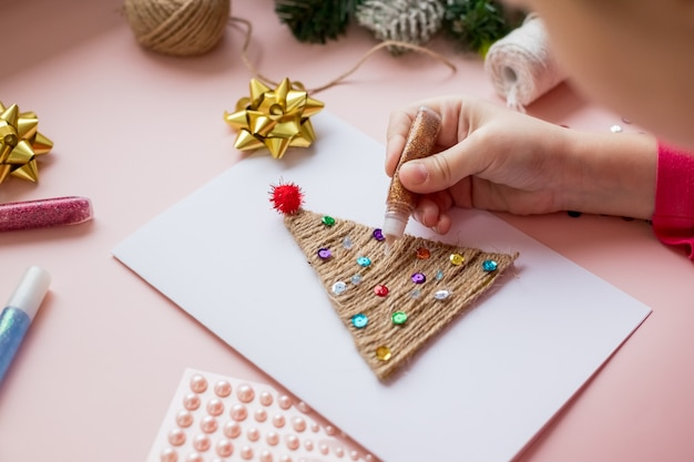Child makes a christmas card for the winter holidays. diy crafts and crafts for christmas do-it