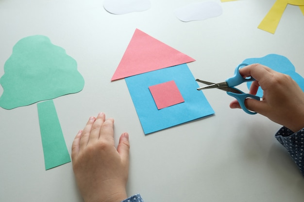 Child makes a craft from colored paper