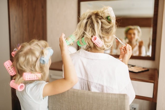 Child makes a funny hairstyle to her mother against a mirror in bedroom at home, toy hair salon. parent feeling, togetherness, happy times