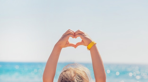 Child makes a heart with her hands