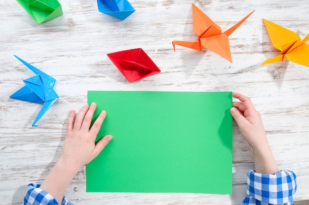 Child makes origami from colored paper. creativity concept.