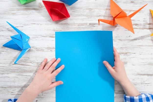 Ребенок делает оригами из цветной бумаги на деревянном столе