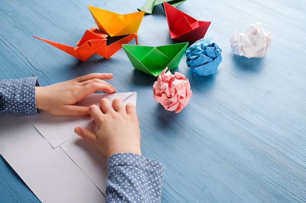Child makes origami from colored paper