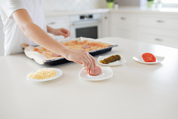 A child makes a pizza. salami, cheese, ketchup, tomatoes, cucumbers.